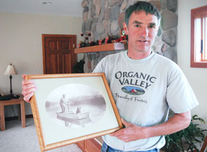 Robert Schmid is holding a photo of his great grandfather on a boat with his pet black bear