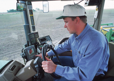 This is a photo of a man working with his GPS system in his truck. Adoption of GPS guidance systems reduces nutrient and pesticide losses.