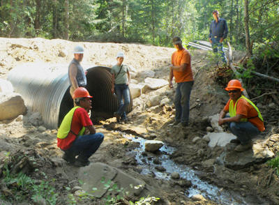 Picture of crew discussing the fully-installed fish passage culvert replacement, Omak watershed.