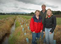 Jason, Brooke, and Debbie VanderVeen stand amid a newly planted buffer strip on their farm.