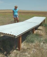 "Nicole Berg checks the water level at one of the wildlife ""guzzlers� the family has installed across their farm."