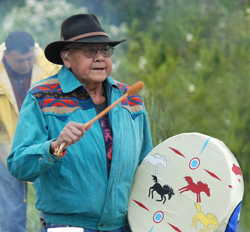Image: Colville Tribal Member playing drum.