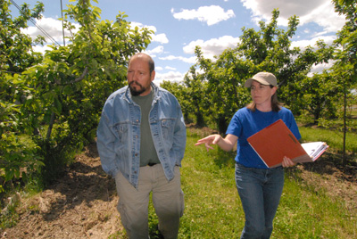 Mr. Alvarez and NRCS Resource Conservationist, Amanda Ettestad review the farm's conservation plan while walking amid rows of organically grown apples.
