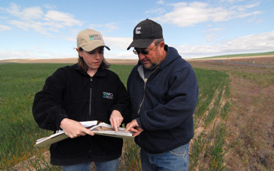 NRCS Resource Conservationist, Amanda Ettestad (left) and Horse Heaven Hills farmer, Don Walker, review the conservation plan that Mr. Walker uses as part of his direct-seed operation. The conservation plan also serves as a guide to maintain the vegetative buffer strips that reduce wind erosion.