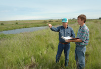 Marvin Willms, left, and NRCS Soil Conservationist Steve Sprecher review the Willms' conservation plan near one of the WRP ponds on the farm.