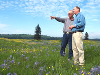 Fred Colvin (left) and NRCS State Conservationist, Gus Hughbanks, look across a sea of blue camas and yellow buttercup flowers at the Colvin Ranch near Tenino. Thanks to the Grassland Reserve Program, the Colvin Ranch will remain as a