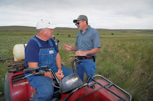 Gerald Davis, left, and NRCS resource conservationist Sergio Paredes discuss invasive species weed control in a field enrolled in the Conservation Reserve Program.
