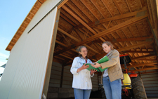 Image: Naomi Ferreira (left) and NRCS Soil Conservationist Lisa Schuchman review the farm's conservation plan in the shade of a recently built waste storage facility.