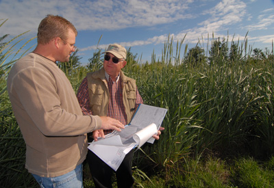 Jeff Schulke, left, and NRCS Soil Conservationist Jim Loiland review the conservation plan that provided the blueprint for the remarkable terrestrial transformation along Dry Creek.