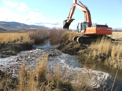 With the grade control structures in place, a backhoe operator breaches a temporary de-watering dam, allowing water from Mid-Toppenish Creek to flow along its historic channel. (Photo courtesy Tracy Hames).