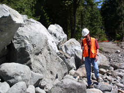 Dean Renner, NRCS Stream Mechanics Engineer, examines the rock vane structures designed to prevent further erosion of the river bank by diverting the water current.