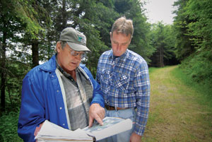 NRCS resource conservationist Nick Somero, left, and John Keller review the forest's conservation plan, which serves as a blueprint for planned conservation activities.