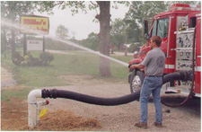 A volunteer firefighter demonstrates the proper technique of spraying down a wildfire. The source of the water, a dry hydrant, is made possible thanks in large part to the Upper Columbia RC&D.