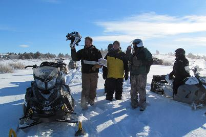 Josh White (left), Sean Black (center), and Chris Black (right) discussing juniper treatment area and project goals while on a January habitat tour of the property via snowmobile.