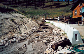 Rock-lined channel with barriers after a debris flow.