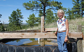 Photo of producer, Charlene Rich, at her EQIP-contracted water tank.