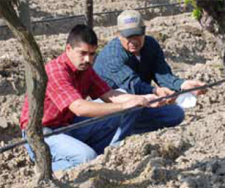 Ramos checks the flow of water with NRCS Soil Conservationist Hugo Calvillo (left).