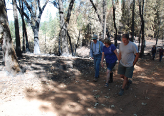 NRCS District Conservationist Mike Brenner and Landowners Jody and Jeff Schnell walk along the fire line.