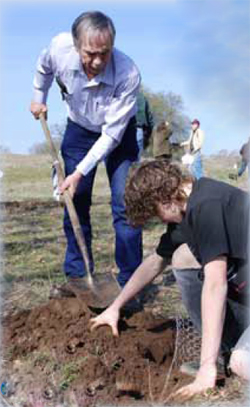 Coarsegold RCD President Tom Wheeler joins a student to plant an elderberry bush.