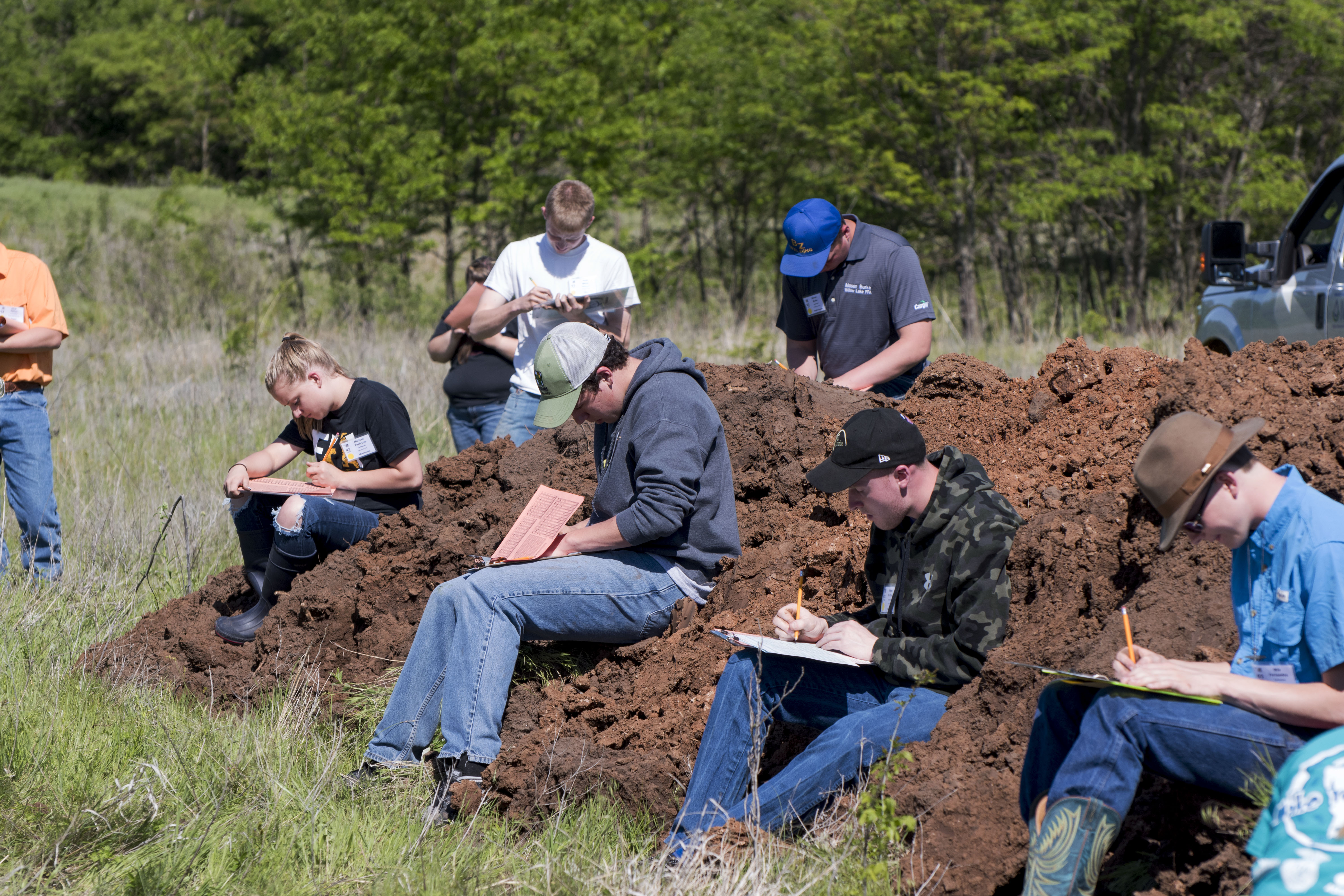 Land judging contestants sit on a mound of soil