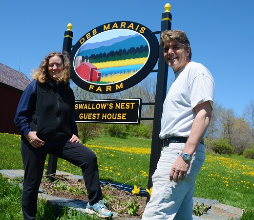 Lyn and Jim Des Marais of Brandon, Vermont stand next to a sign on their 1,250 acre farm in the Otter Creek Watershed.
