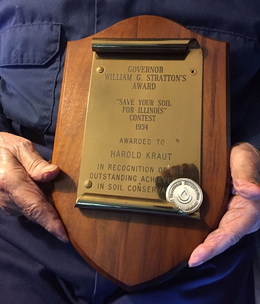Harold Kraut holds an award presented to him in 1954 by Illinois Governor William Stratton, for his outstanding achievements in soil conservation. State leaders evaluated farms statewide, and Calhoun County ranked #2 for the best conservation farms.
