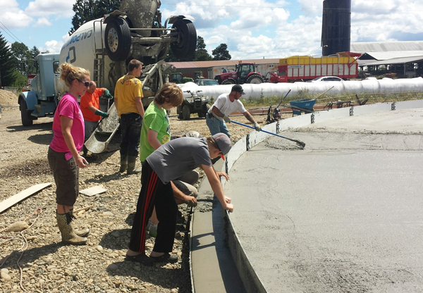 The Johnson family adding their final touch to the freshly-poured concrete of their waste storage tank.