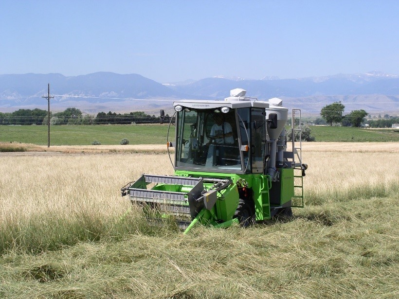 Image of combine harvesting native grass with mountains in the background