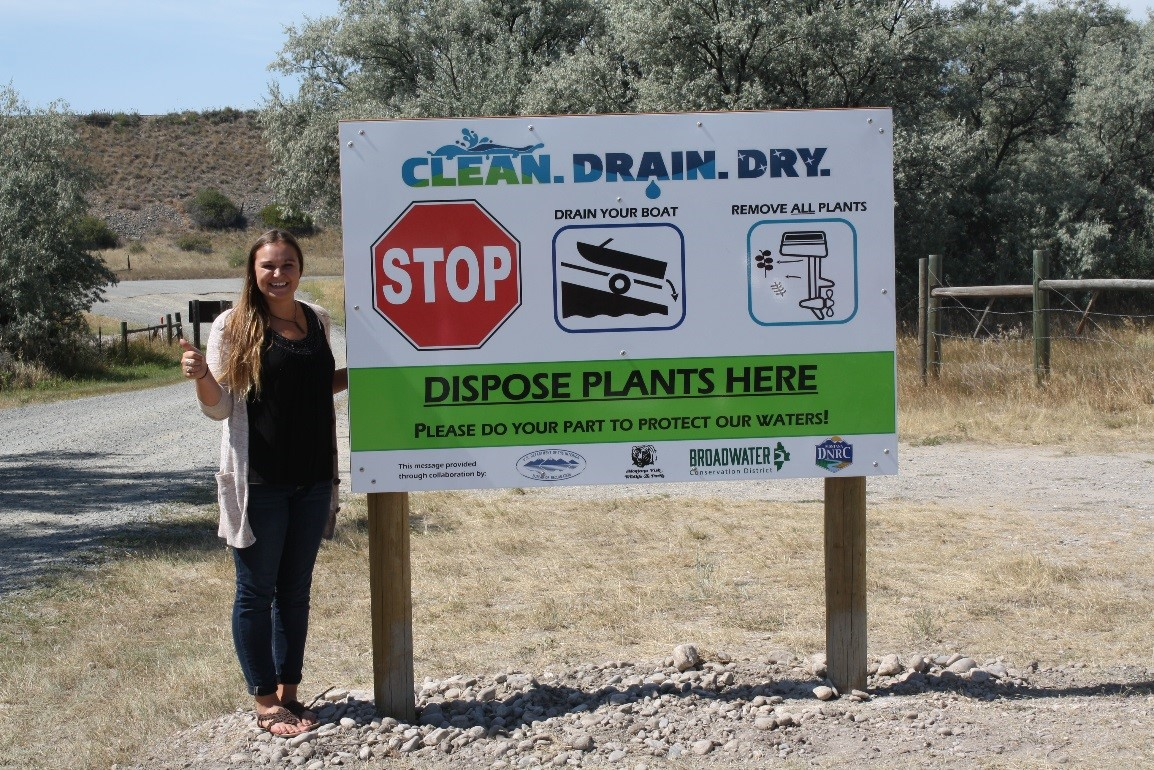 Volunteer Katie Mumford stands beside an educational sign she helped create. NRCS photo.