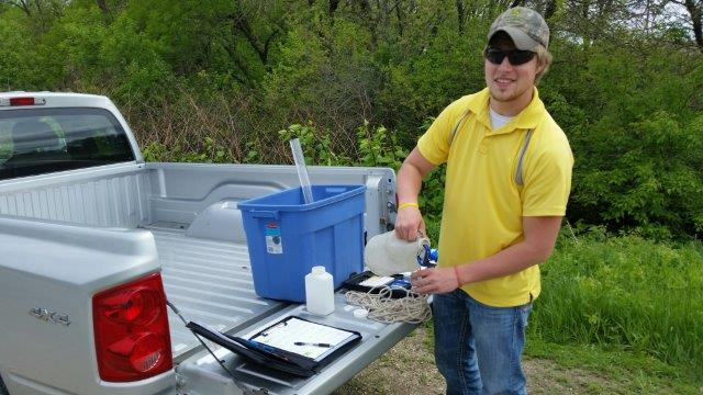 Volunteer Derek Grube collects samples of water for testing. NRCS photo.