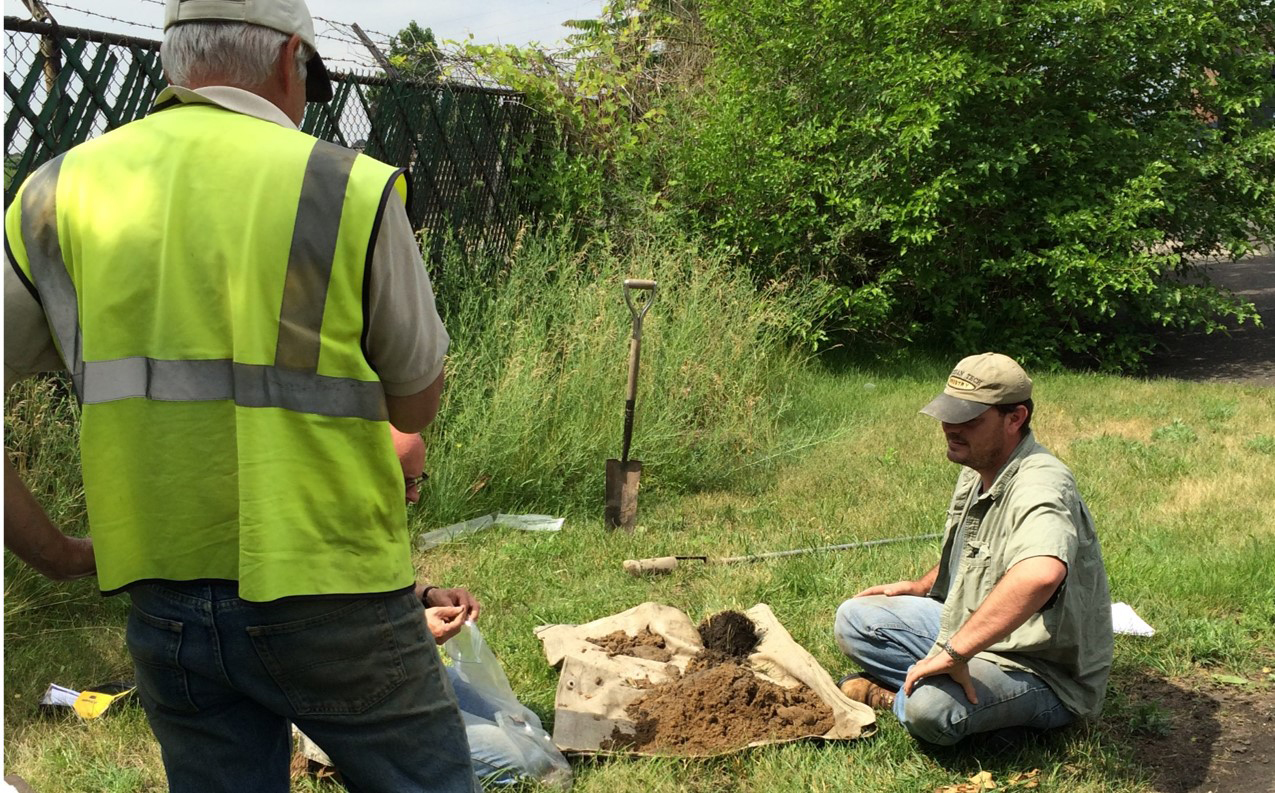 Joe Calus and Eric Gano with NRCS examine buried soil in a park in Wyandotte. NRCS photo.