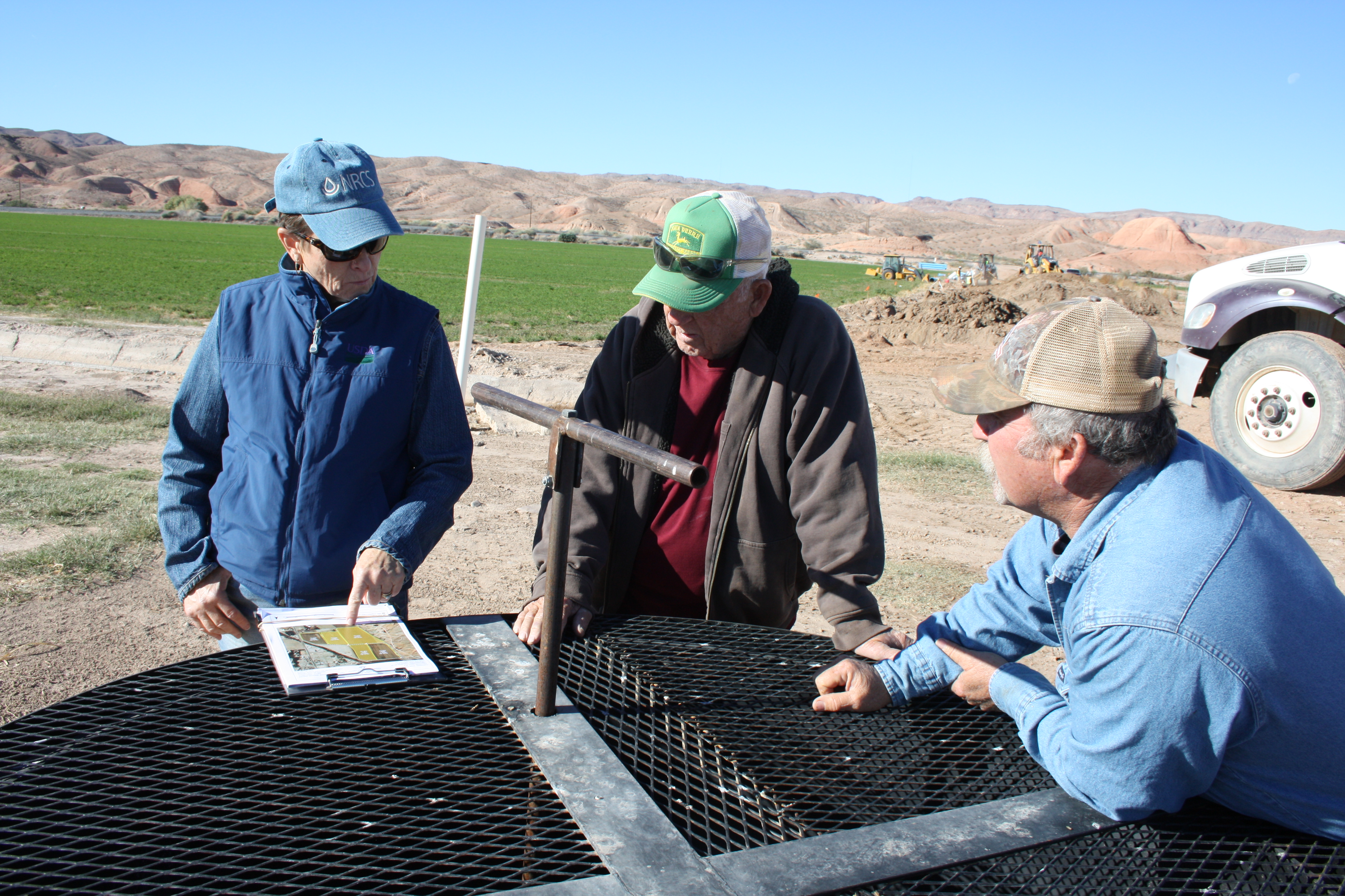 Teri Knight, district conservationist, and the Hardys gather around a water control structure to discuss pipeline installation plans.