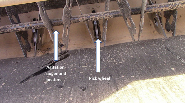 Native seed boxes with aggressive agitation and pick wheels that reach in and pull seed into drop tubes are the most reliable when planting fluffy native seed. Left arrow points to agitation auger and beaters and right arrow points to pickwheel