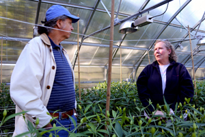 Steve Spear of NRCS chats with Rebecca Perry in her greenhouse.