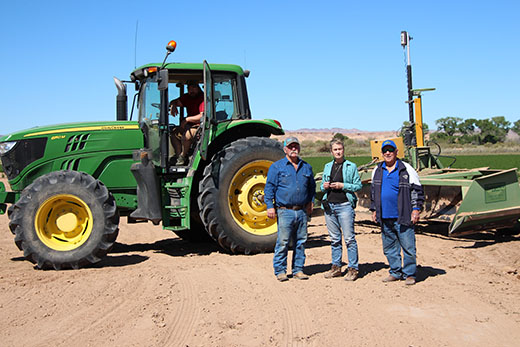 USDA NRCS' District Conservationist Teri Knight (middle) stands with the Hardys in southern Nevada where they are laser leveling with assistance through NRCS
