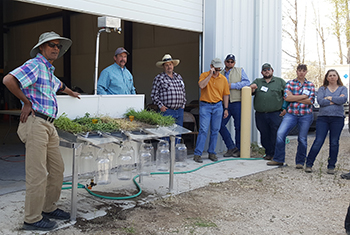 NRCS students watch trainer in plaid shirt and hat standing by rainfall simulator with grass and bare soil to demonstrate erosion into glass jars once water is applied.