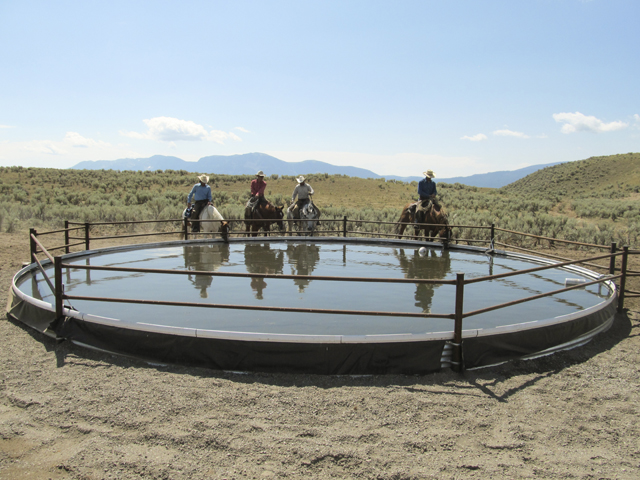 Four men on horses in front of a circular, in ground livestock watering facility