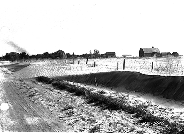 Image showing wind and soil erosion near a farmstead with some drifts a depth of 4 feet that nearly cover the fenceline.