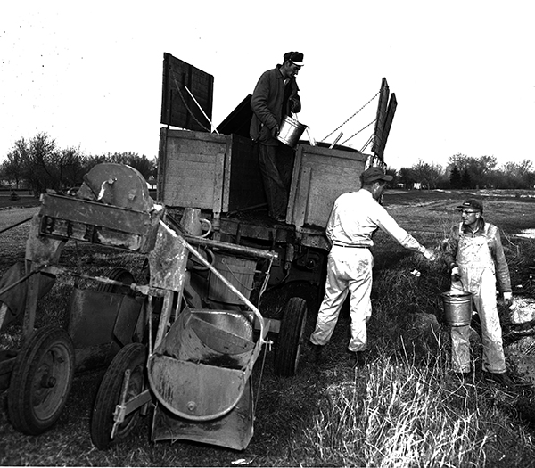 Image of three men wetting down trees with buckets of water from the river before days planting started - wildlife planter and district truck, Eddy County, ND
