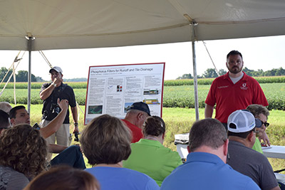 People seated under a tent in a field, for a presentation on phosphorus filters for runoff and tile drainage on Kurt Farm, Hardin County, Ohio.