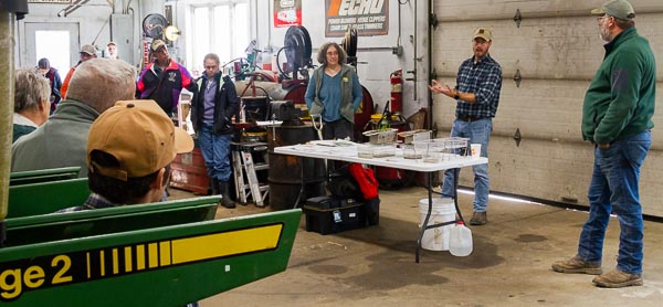 A group of agricultural producers gather in an equipment shed to look at equipment nd talk about soil health principles.