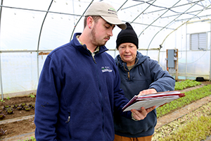A planner and farmer discuss a conservation plan in a high tunnel.