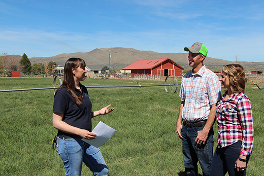 Soil Conservationist Jessica Gwerder speaks with producers on their farm