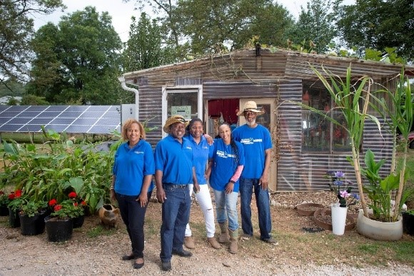 A group of urban agricultural producers stand and pose outside their operation.