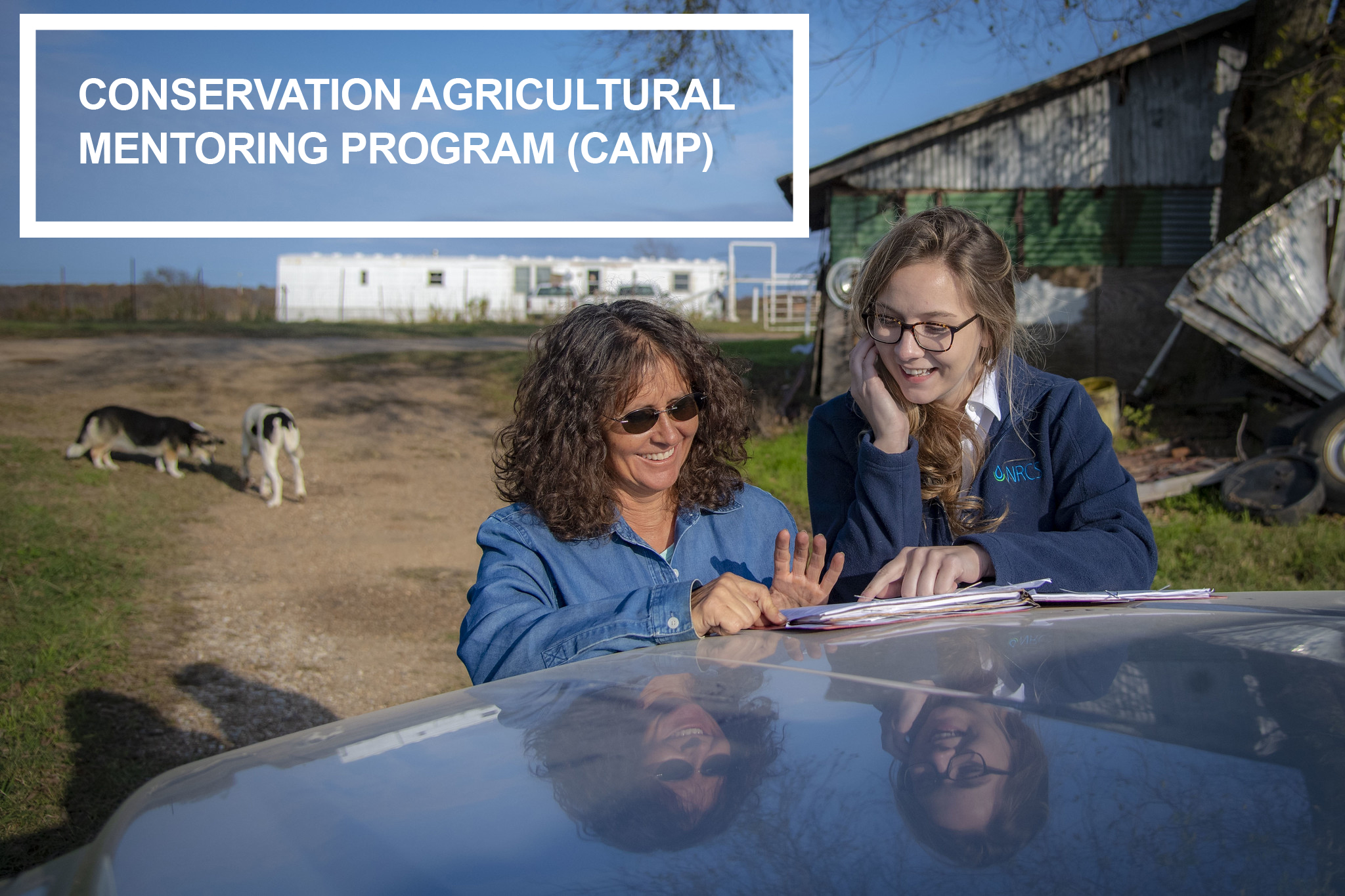 "an image of an agricultural producer and an NRCS employee look over some paperwork on the hood of a vehicle. A Graphic overlay appears in the upper left hand corner that says ""Conservation Agricultural Mentoring Program (CAMP)"""