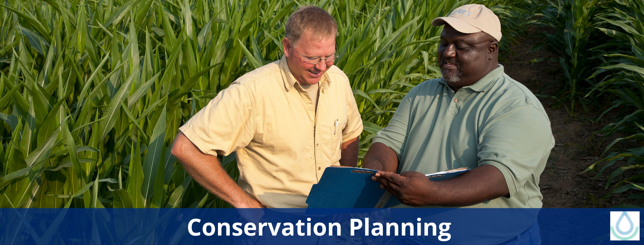 A farmer and an NRCS employee look at a conservation plan while standing in a field.
