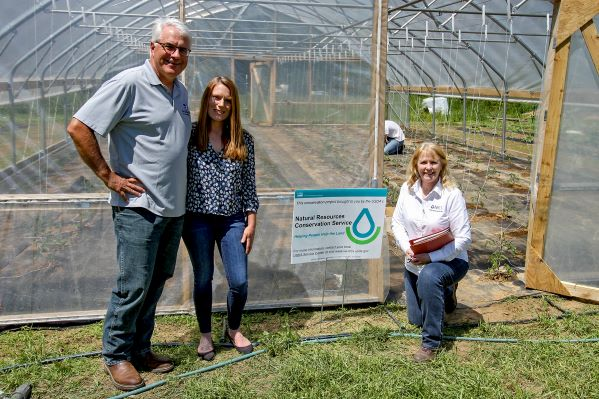 John and Cappie Montgoemry pose with District Conservationist Peggy Shaw-McBee in front of their NRCS-funded high tunnel.