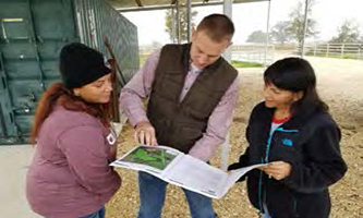 District Conservationist visits with two agricultural landowners about their conservation plan.