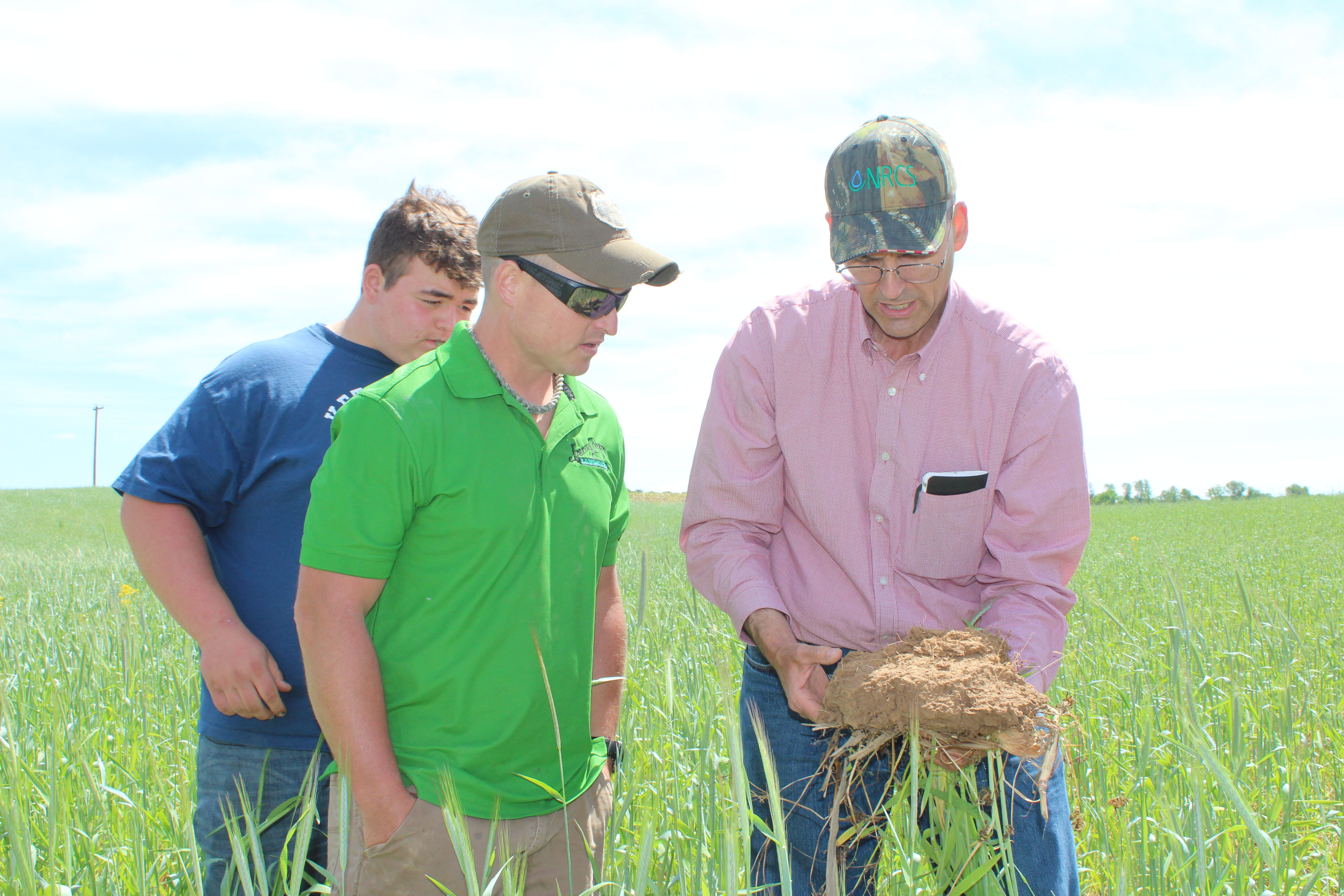 John Graham, soil health specialist, explains about pore space in soil as landowner looks on.