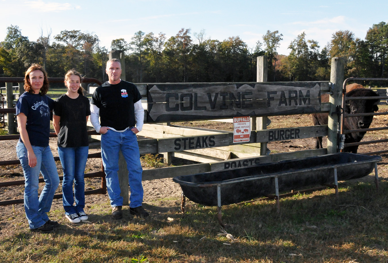 Bison farm owners Bobbi and Allen Lester pose with their daughter in front of the family farm.